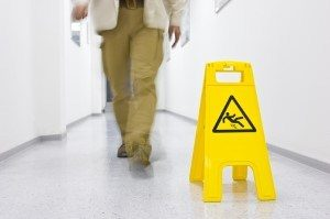 Man next to a slip and fall sign