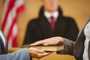 courtroom witness swearing in on bible